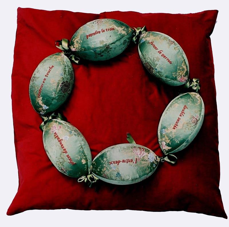 Le bijou de la reine, 2007, 6 ballons de rugby, tissu XVIIIe siècle– soierie lyonnaise, expressions de l'univers du rugby réalisées en broderies en relief – 110 cm x 110 cm x 16 cm (épaisseur),présenté à l'exposition XV – musée Géo-Charles, Echirolles, Isère.